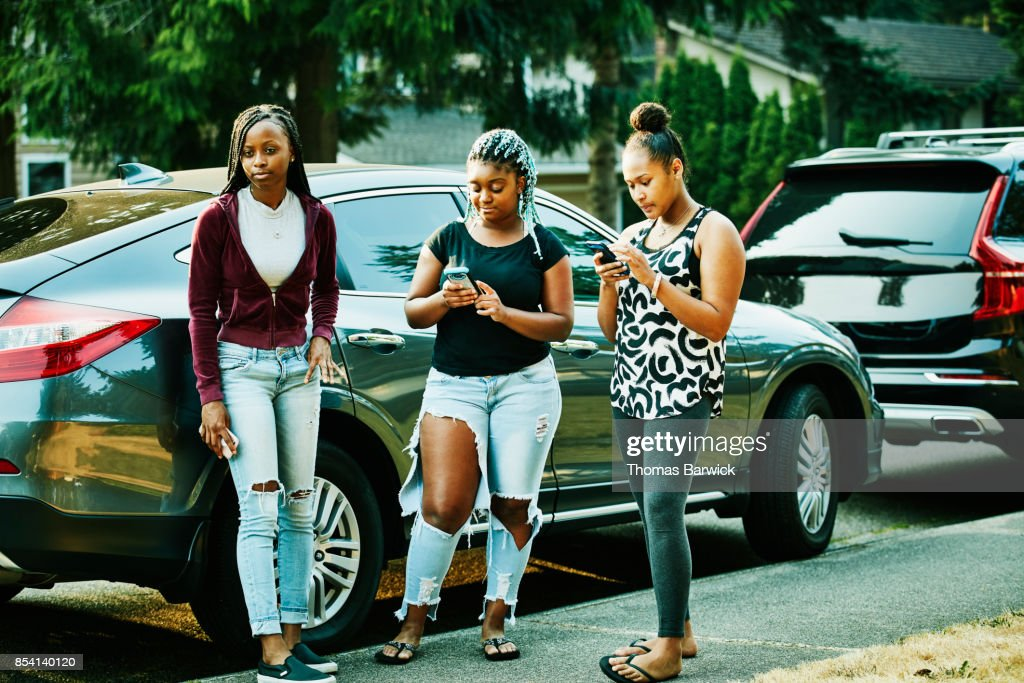 Teenage friends hanging out in front yard on summer evening looking at smartphones : Stock Photo