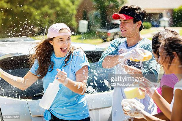 Teenage friends have water fight during car wash