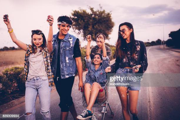 Teenage friends having fun with a shopping cart and confetti