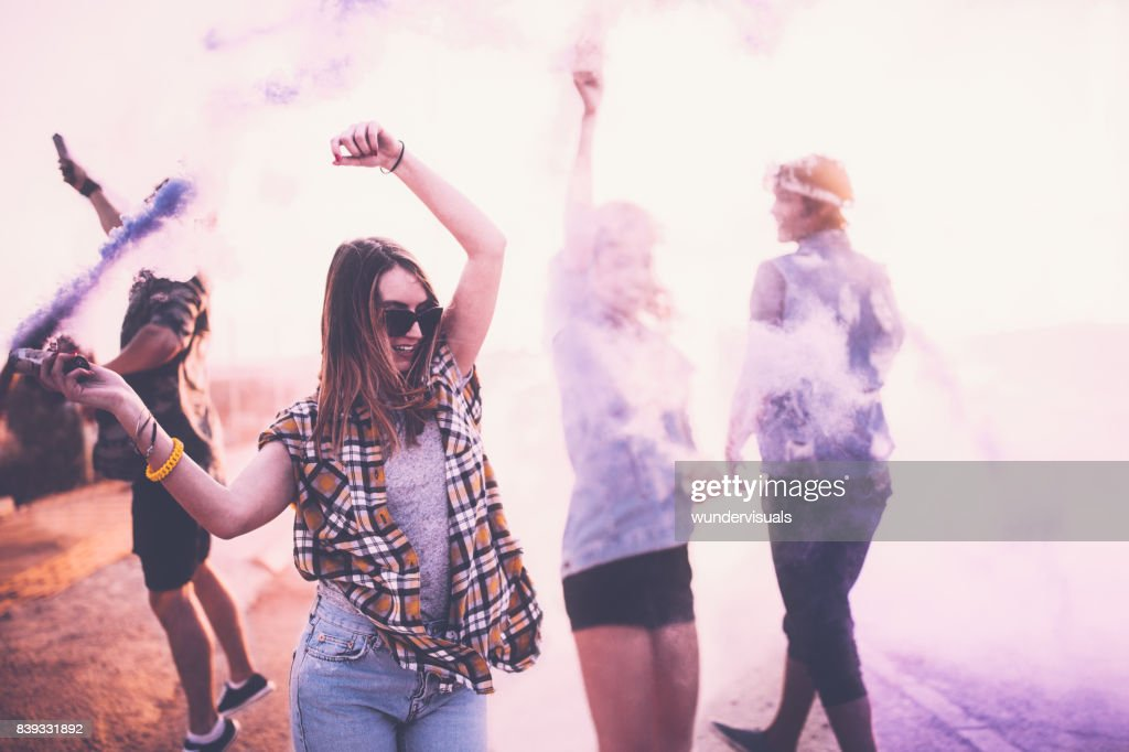 Teenage friends having fun with smoke bombs in city streets : Stock Photo