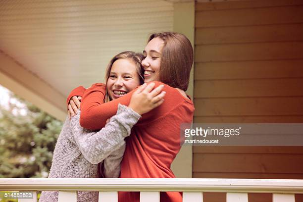 """teenage friends hugging on porch - """"martine doucet"""" or martinedoucet stock pictures, royalty-free photos & images"""