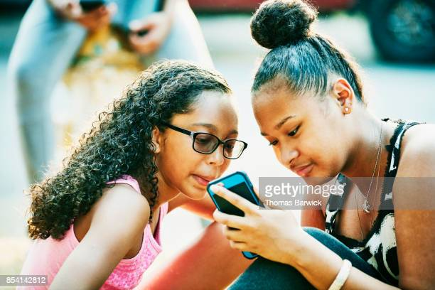 Teenage friends looking at smartphone while sitting in front yard on summer evening