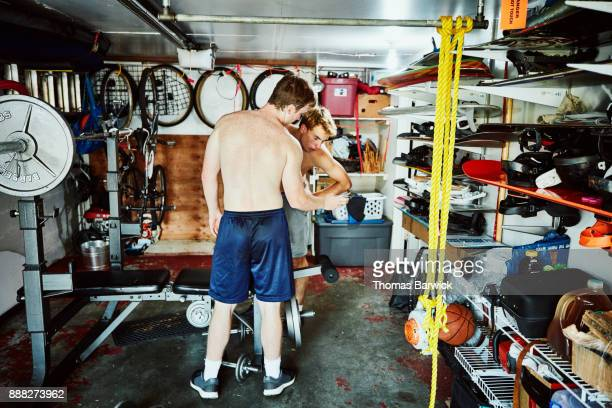 Teenage friends looking at smartphone while working out in gym in garage