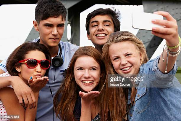 teenage friends photographing themselves with smartphone - indian girl kissing stock photos and pictures