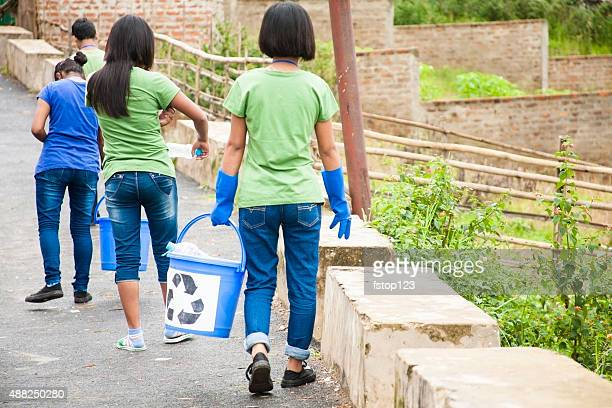 Teenage friends picking up trash to recycle. Roadside setting.