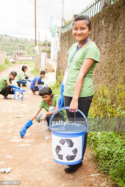 teenage friends picking up trash to recycle. urban roadside setting. - city cleaning stock pictures, royalty-free photos & images
