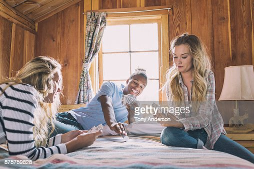 Teenage friends playing cards on bed in rustic cabin