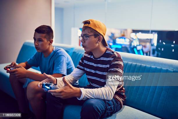 teenage friends playing video game in an amusement arcade - videogiocatore foto e immagini stock