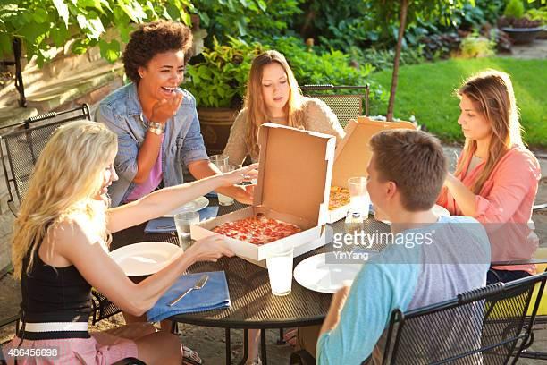 10 代の友人との共有ピザディナーでの夏の裏のパティオテーブル