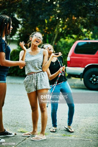 teenage friends singing while hanging out together on summer afternoon - girl wear jeans and flip flops stock photos and pictures