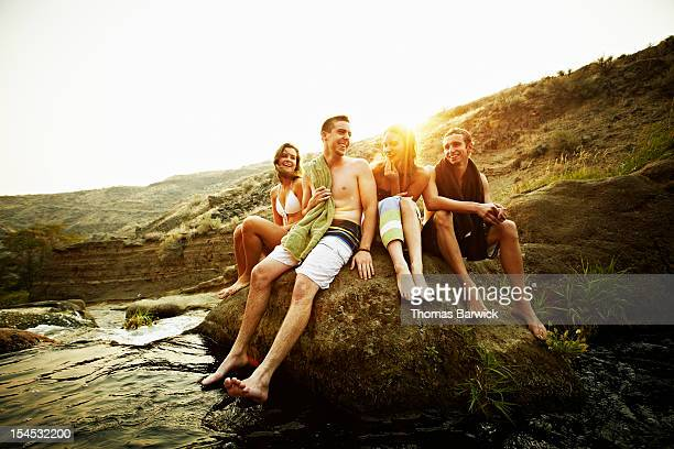 Teenage friends sitting on rock at sunset smiling