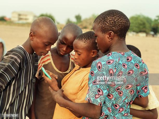 teenage friends using mobile phone while standing at field - africa stock pictures, royalty-free photos & images