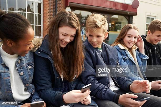 Teenage Friends Using Mobile Phones In Urban Setting