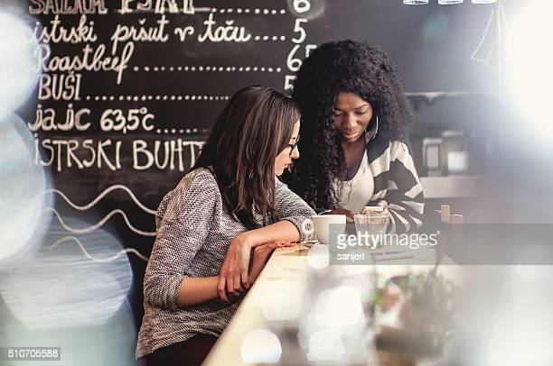 Teenage friends using smartphone at the snack bar