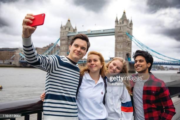 amis d'adolescent visitant londres sur le pont de tour - angleterre photos et images de collection