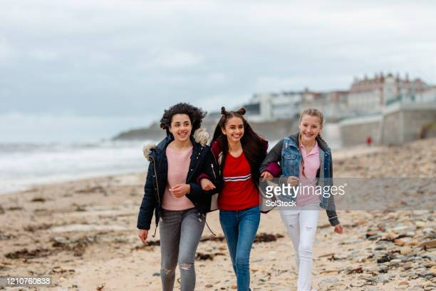 teenage friends walking arm in arm along windy beach - girls stock pictures, royalty-free photos & images