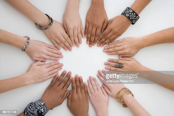 teenage friends with hands placed in a circle - ethnicity stock pictures, royalty-free photos & images