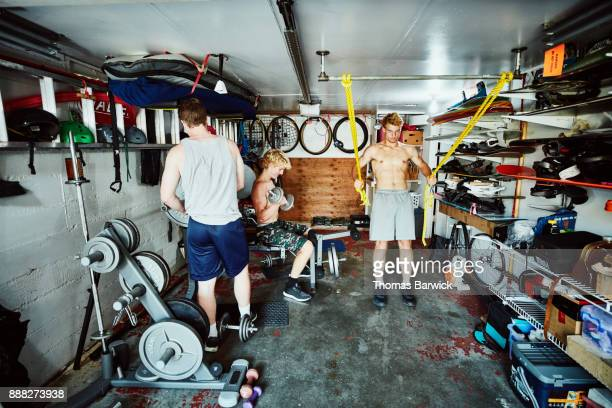 Teenage friends working out together in basement gym