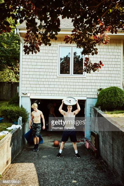 Teenage friends working out together in driveway of home on summer afternoon