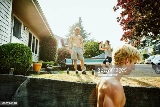 Teenage friends working out together in front yard of home on summer evening