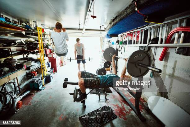 Teenage friends working out together in gym in garage