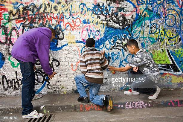 Teenage gang doing graffiti on a wall
