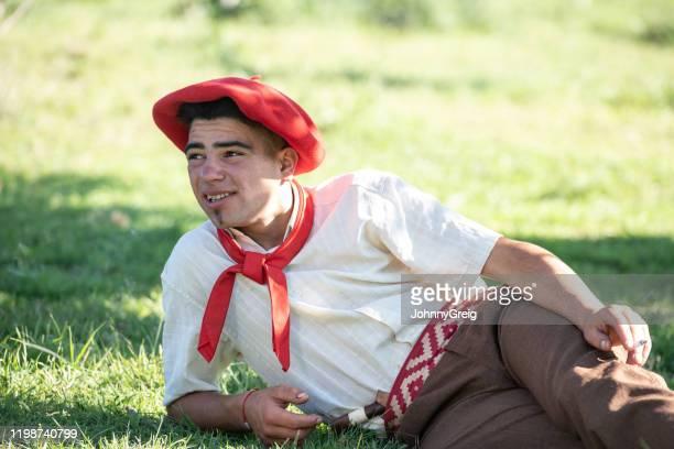 草の中でリラックス伝統的な服を着た十代のガウチョ - ネッカチーフ ストックフォトと画像