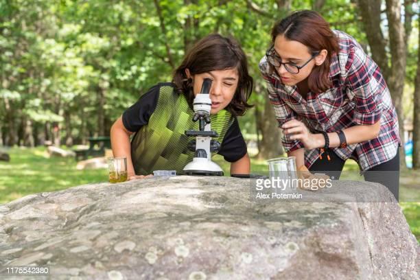 十代の少女、17歳の妹は、晴れた夏の日に湖畔で屋外で顕微鏡と自然を学ぶ方法を彼女の9歳の弟に教えています。 - 16 17 years ストックフォトと画像
