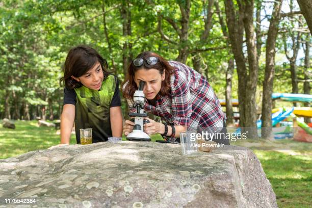 teenage girl, 17-years-old sister teaching her 9-years-old younger brother how to working with a microscope and learning nature outdoors at the lakeshore in the sunny summer day. - 16 17 years stock pictures, royalty-free photos & images
