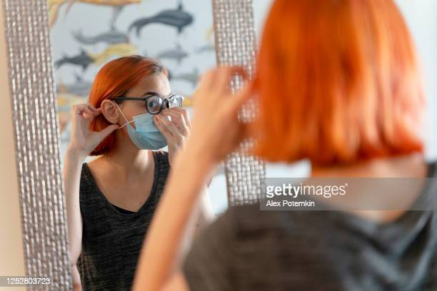 a teenage girl, a 17-years-old caucasian with red died hair, putting on a protective mask in front of a mirror. - 16 17 years stock pictures, royalty-free photos & images