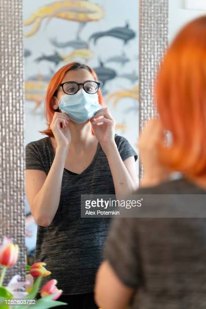 a teenage girl, a 17-years-old caucasian with red died hair, wearing a protective mask in front of a mirror. - 16 17 years stock pictures, royalty-free photos & images