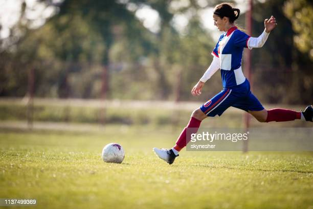 teenage girl about to kick soccer ball on a playing field. - tirare in rete foto e immagini stock