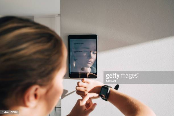 teenage girl adjusting smart watch with digital tablet mounted on white wall at home - smart stock pictures, royalty-free photos & images