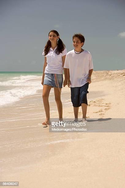 teenage girl and a boy walking on the beach - girls with short skirts - fotografias e filmes do acervo
