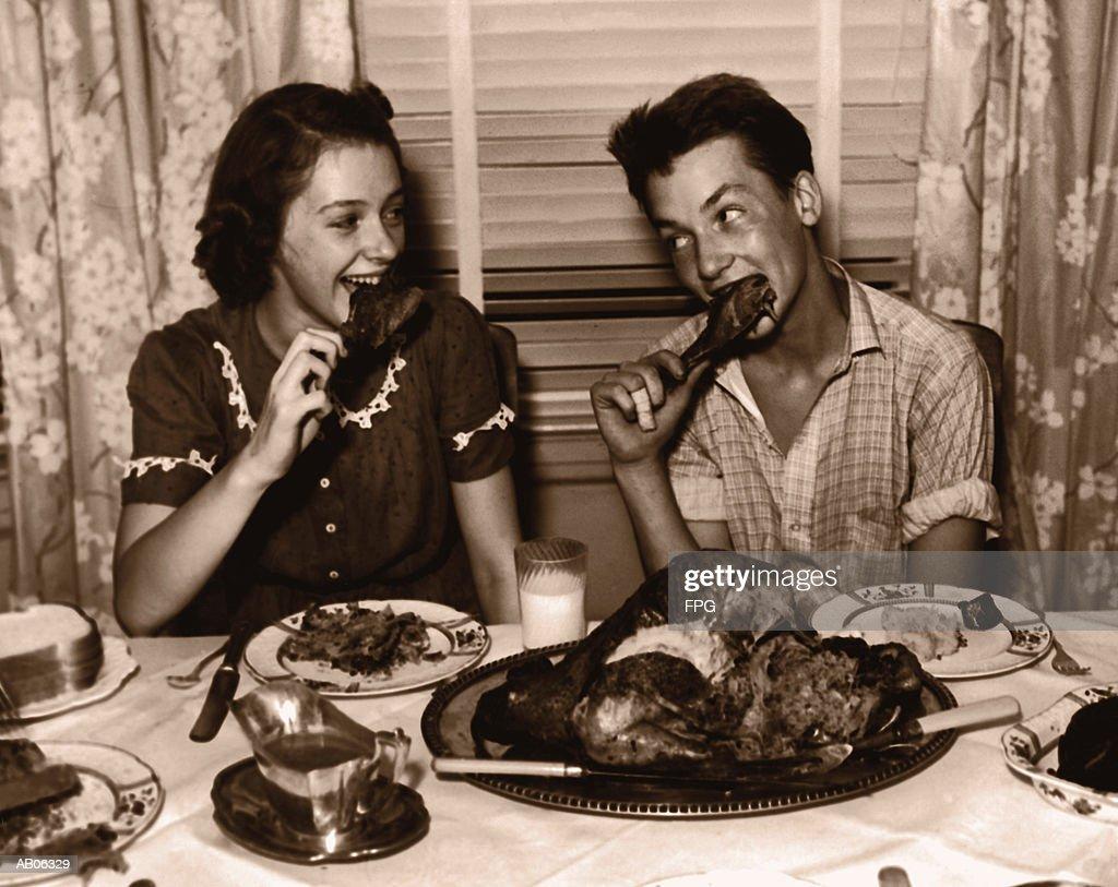 Teenage girl and boy (15-17) eating turkey dinner (B&W sepia tone) : Stock Photo