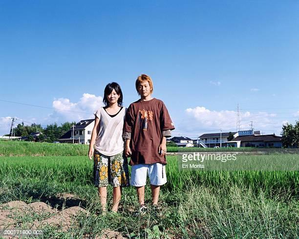 Teenage girl and boy (16-18) in open field, portrait