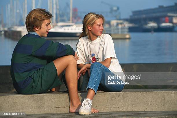Teenage girl and boy (16-17) sitting by harbour looking away
