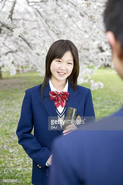 Teenage girl and boy standing under cherry trees, girl holding a diploma, front view, rear view, Japan