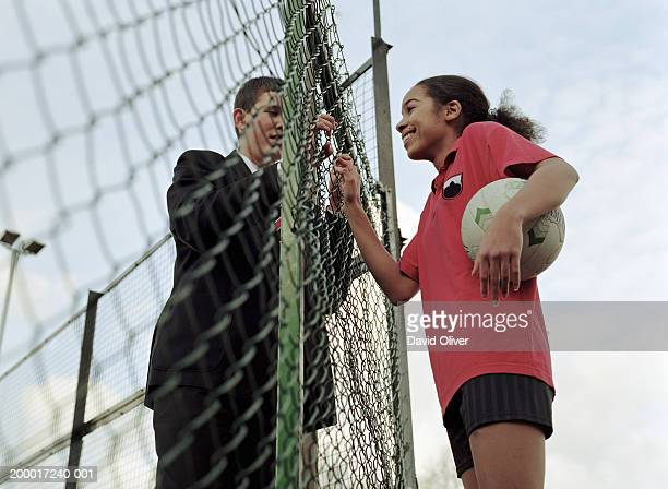 Teenage girl and boy (13-15) talking through sports court fence