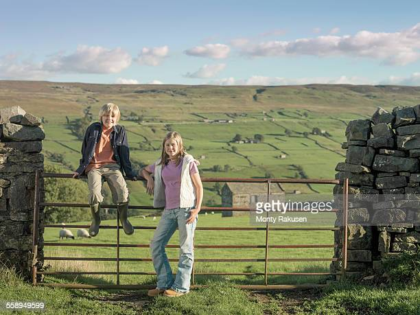 teenage girl and brother at gate in rural landscape - monty rakusen stock pictures, royalty-free photos & images