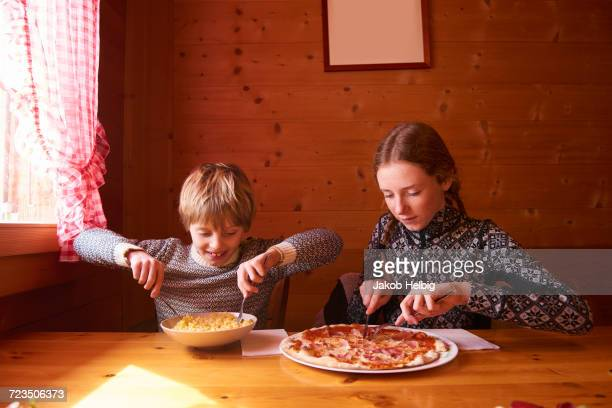 Teenage girl and brother eating pasta and pizza at chalet table