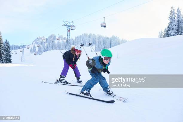Teenage girl and brother skiing down ski slope, Gstaad, Switzerland