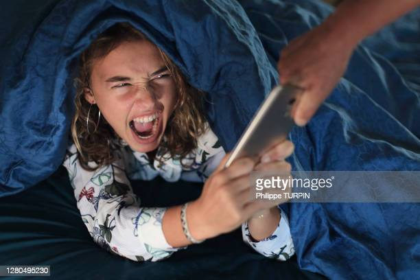 teenage girl and everyday life. in bed with smartphone - catching stock pictures, royalty-free photos & images
