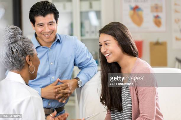 teenage girl and father laugh with pediatrician - cardiologist stock pictures, royalty-free photos & images