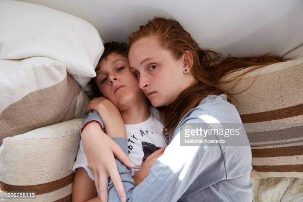 Teenage girl and her little brother cuddled together on a daybed in their home, looking very sleepy.