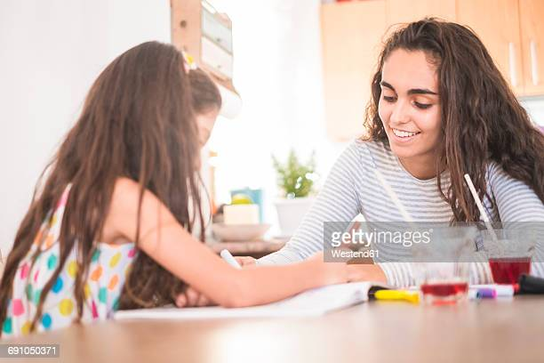 Teenage girl and her little sister drawing together