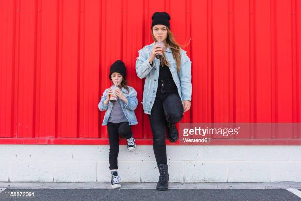 teenage girl and little sister leaning against red wall drinking cocoa - representar - fotografias e filmes do acervo