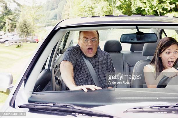 Teenage girl (14-16) and man screaming in car