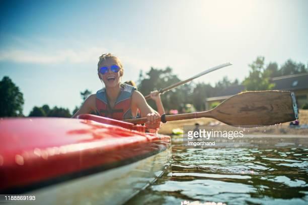 adolescente e madre che si godono il kayak sul lago - kayak foto e immagini stock
