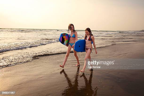 Teenage girl and sister carrying surfboards on beach, Goa, India